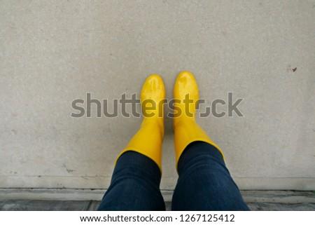 Yellow Wellies  Rainboots Outside on the wet sidewalk