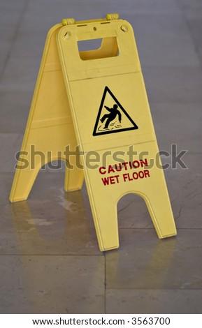 Yellow wet floor sign on marble floor