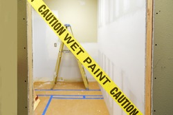 Yellow wet paint caution tape across a doorway with construction ladder in the background