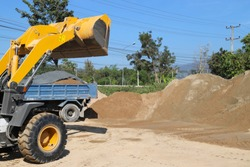 Yellow wheel loader moving to carry up sand from sand pile in sunny day with blue sky.