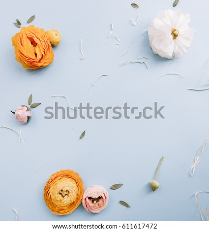 Stock Photo Yellow white and pink Ranunculus flowers and eucalyptus on the light blue background, flat lay with a blank space in the middle