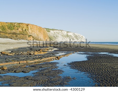 yellow, white cliff with rock ledge and blue sea in foreground