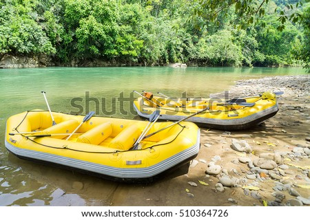 Yellow white water raft static at shaded with shadows under the tree near riverbank of adventure river called Kiulu River in Sabah Malaysian Borneo