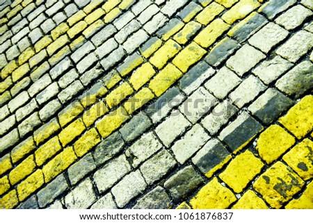 yellow white zebra on paving stones #1061876837