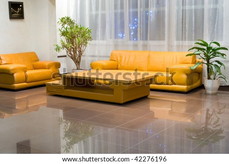 Yellow wide leather sofa, armchair and coffee table in hall interior. The picture on the wall is by the photographer and was inserted here with a graphic program.