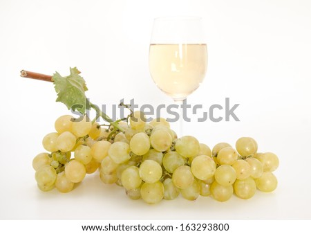 Yellow wine with grapes and vine leaf