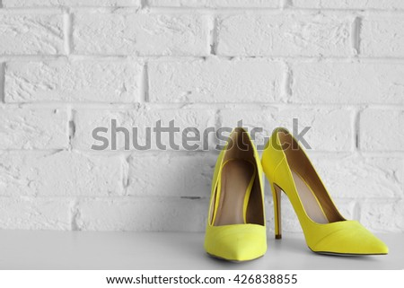 Yellow woman high heels on a brick wall background #426838855