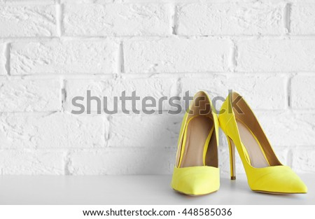 Yellow woman high heels on a brick wall background #448585036