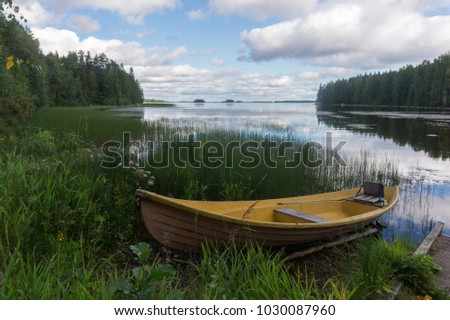 Yellow wooden boat on the shore of a picturesque lake and a reflection of clouds #1030087960