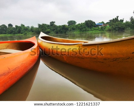 yellow wooden canoe parking, evening river view, wild air, forest trees line riverside and reflection in water nobody, countryside Thailand, cool destination place to kayak on vacation, inspire myself