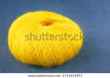 Yellow yarn ball of mohair (angora) wool for knitting on the velvet background. Front view.
