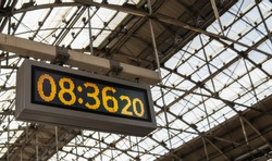 Yellowish digital clock  with old classic style at the train station.