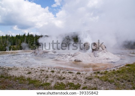 Yellowstone geothermal geyser erupting on background of steam, smoke and clouds - stock photo