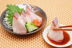 Yellowtail sashimi. A traditional Japanese dish. Cucumber, carrots, Perilla, and radish.