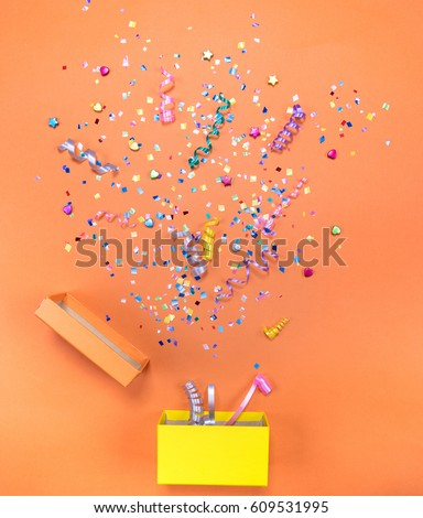 Yelow gift box with various party confetti, streamers, noisemakers and decoration on a orange background. Colorful celebration background. #609531995