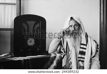 Yemenite Rabbi, in traditional robes and prayer shawl, listening to radio, ca. 1937.