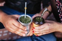Yerba mate tea in bombilla. Special metal straw. Sout America popular hot drink. Couple drinking healthy herbal beverage. Engagement outdoor picnic.