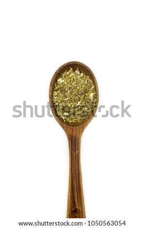 Yerba Mate Tea on wooden spoon isolated on white background. Dried yerba mate tea powder.  #1050563054