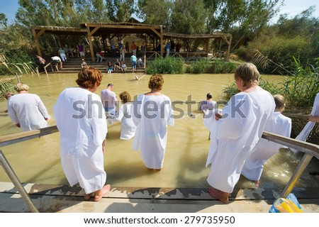YERICHO, ISRAEL - OCT 15, 2014: Religious christians with white clothes going into the water of the Jordan river at baptismal site Qasr el Yahud near Yericho