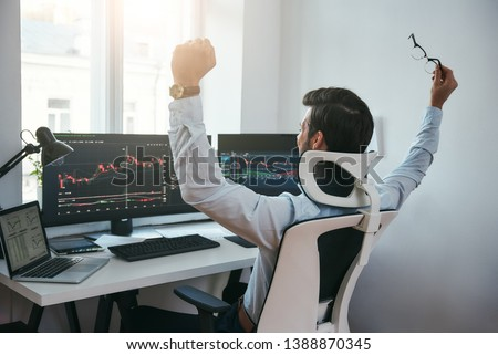 Yes! Back view of stock trader with raised hands looking at multiple computer screens with data and charts and feeling happy while sitting in modern office