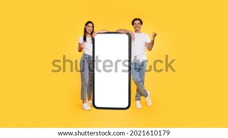 Yes. Excited Couple Leaning On Big Smartphone With Empty White Screen Shaking Clenched Fists, Cheerful Guy And Lady Celebrating Win, Standing On Yellow Background, Mock Up Collage, Full Body Length