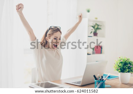 Yes! Happy excited woman at home workstation triumphing with raised hands