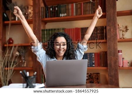 Yes, I'm A Winner. Excited emotional ecstatic lady celebrating success, victory or great news sitting at table, using personal computer, screaming yeah and raising hands up. Smiling happy woman in joy Foto stock ©
