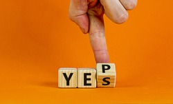 Yes or yep symbol. Businessman turns a cube, changes the word 'yes' to 'yep'. Beautiful orange background. Copy space. Business, motivation and yes or yep concept.