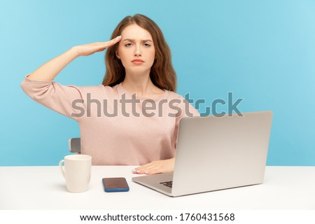 Yes sir! Obedient responsible young woman employee sitting at workplace with laptop and giving salute, listening to boss order, corporate discipline. indoor studio shot isolated on blue background Сток-фото ©