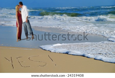 Yes written in sand with couple and waves in background
