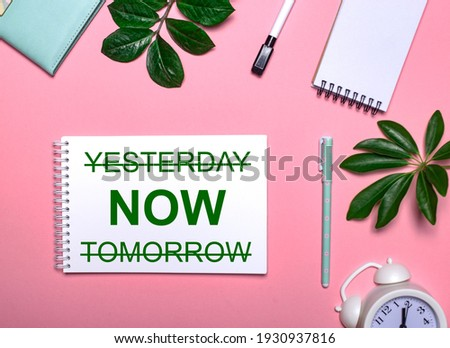 YESTERDAY NOW TOMORROW is written in green on a white notepad on a pink background surrounded by notepads, pens, white alarm clock and green leaves. Educational concept ストックフォト ©