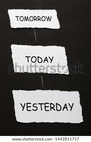 Yesterday Today Tomorrow text on 3 piece of torn paper over black surface. #1442815757