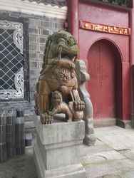 Yibin, Sichuan, China - July 10 2018: A stone lion dog guardian statue and cub on a post at Hui Guang Temple in ancient Lizhuang District of Yibin City in Sichuan