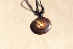 Yin Yang pendant necklace brown color handmade shoot outside in a sunny day closeup. Selective Focus