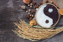 Yin Yang sign with black rice and jasmine white rice  on wooden background. Concept healthy eating,organic food