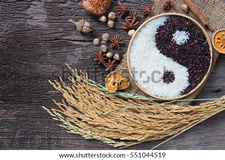 Photo of  Yin Yang sign with black rice and jasmine white rice  on wooden background. Concept healthy eating,organic food