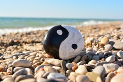 yin yang symbol painted on a rock on the sea beach on a sunny day
