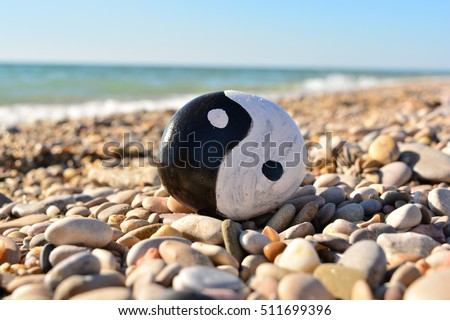 yin yang symbol painted on a rock on the sea beach on a sunny day #511699396