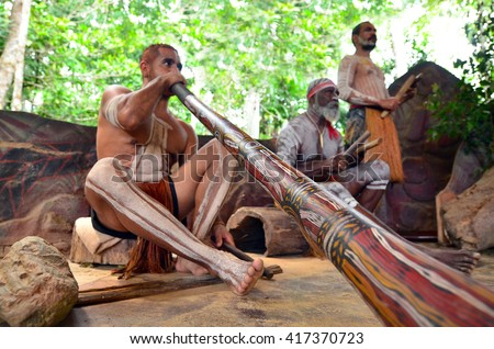 Yirrganydji Aboriginal men play Aboriginal music on didgeridoo and wooden instrument during Aboriginal culture show in Queensland, Australia.