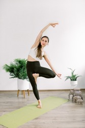 Yoga and fitness concept, Vrksasana or tree pose. Front view of slim pretty girl, doing yoga tree pose, gesturing mudra, standing in modern light studio, full length