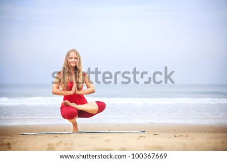 Yoga Ardha Baddha Padma Padangusthasana balancing on toes by young woman with long hair in red cloth on the beach at ocean background