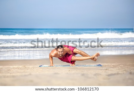 Yoga astavakrasana eight angle pose by fit man with long hair in red trousers on the beach at ocean background
