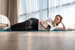Yoga at home. A young woman in sportswear is lying sideways on a sports Mat and using a smartphone. Windows in the background. Side view. Copy space
