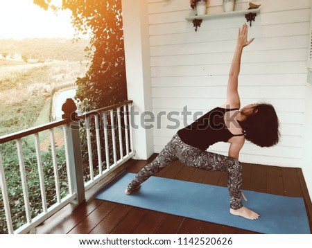 Yoga at home, keep clam, attractive young woman exercise stretching on yoga mat at home with natural view #1142520626