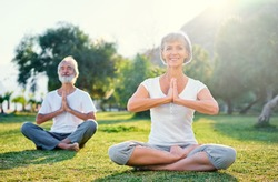 Yoga at park. Middle aged family couple  sitting in lotus pose on green grass. Concept of pray and meditation.