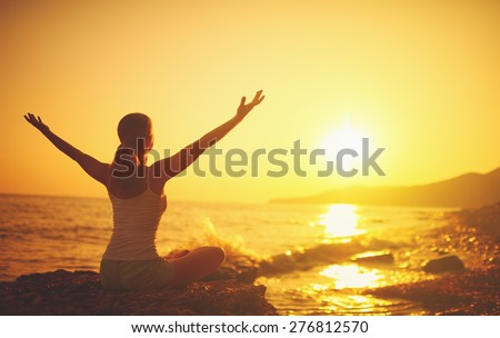 yoga at sunset on the beach. woman doing yoga, performing asanas and enjoying life on the sea