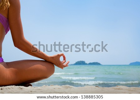 yoga background, woman in lotus position meditating on the beach