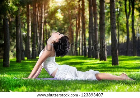 Yoga bhujangasana cobra pose by woman in white costume on green grass in the park around pine trees