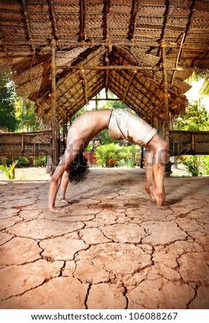 Yoga chakrasana wheel pose by fit man in white trousers on the drought earth in yoga shala, Varkala, Kerala, India