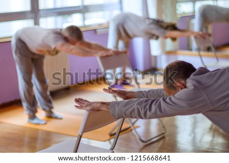 Yoga class, downward facing dog with the help of a chair done by three practitioners.
